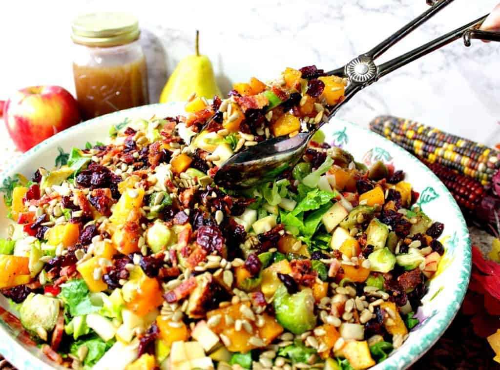Salad tongs holding a large portion of fall chopped salad with Brussels sprouts, dried cranberries, and bacon.
