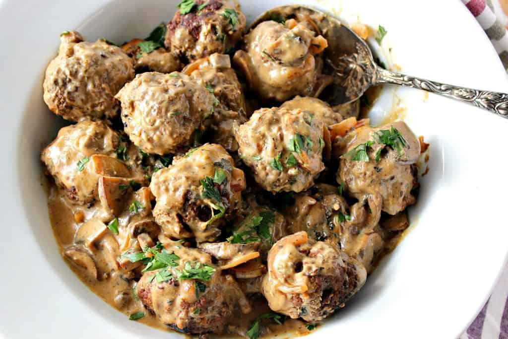 Overhead photo of a bowlful of German meatballs with parsley and a large serving spoon.
