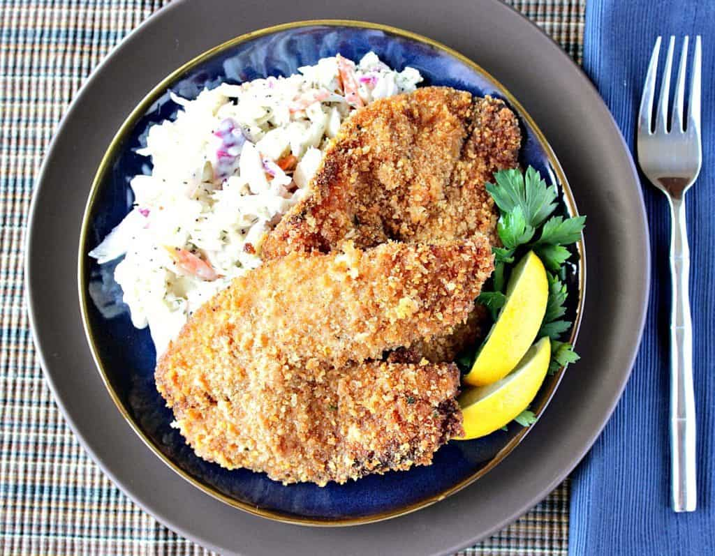 Overhead photo of a plate of homemade fried tilapia along with lemon wedges and coleslaw.