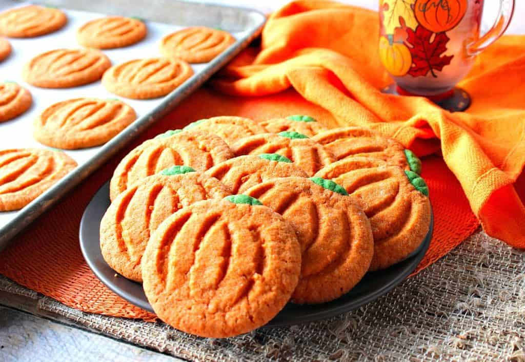 A horizontal image of a plate filled with orange and green pumpkin shaped sugar cookies with an orange napkin and a textured place mat.