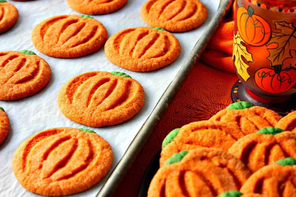 A horizontal image of a tray of pumpkin-free sugar cookies with a pumpkin and leave coffee mug.