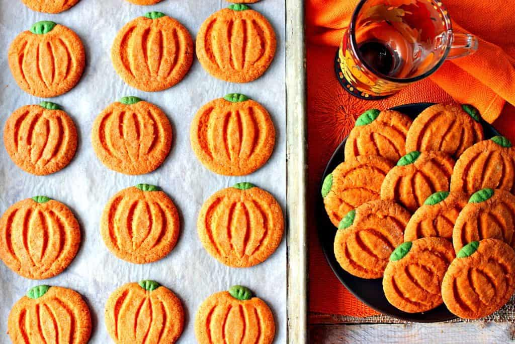An overhead picture of a tray of pumpkin-shaped pumpkin cookies along with a plate filled with them.