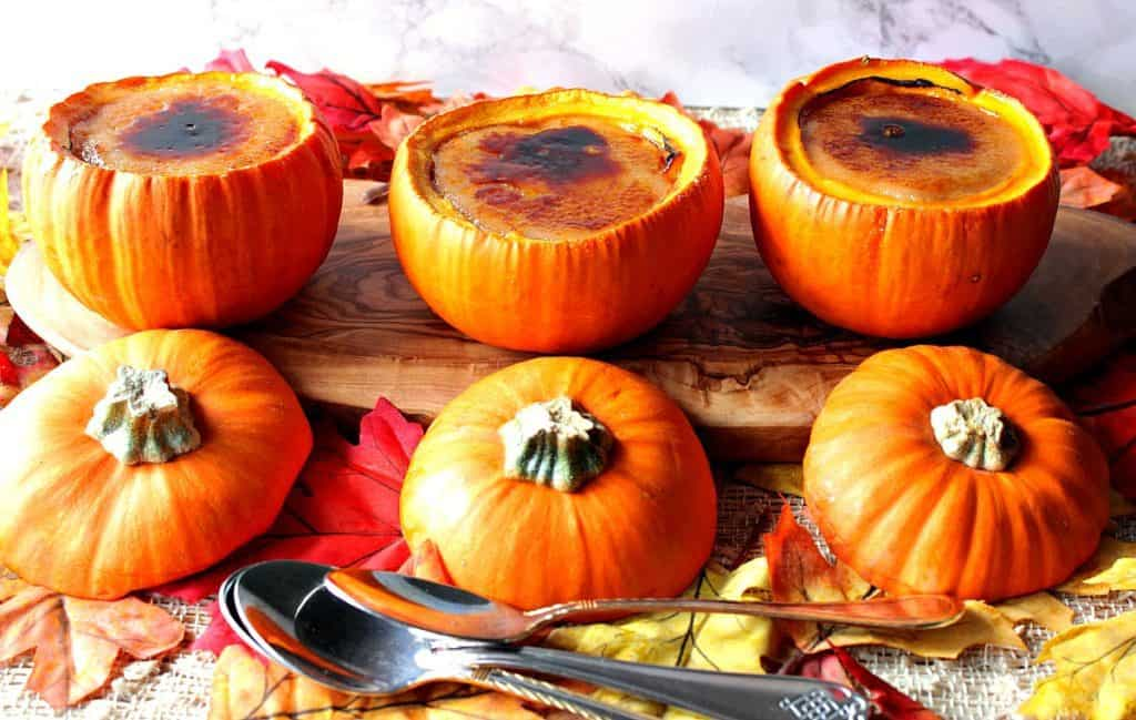 Three pumpkin creme brulee baked in real pumpkins lined up on a board with autumn leaves and pumpkin tops.