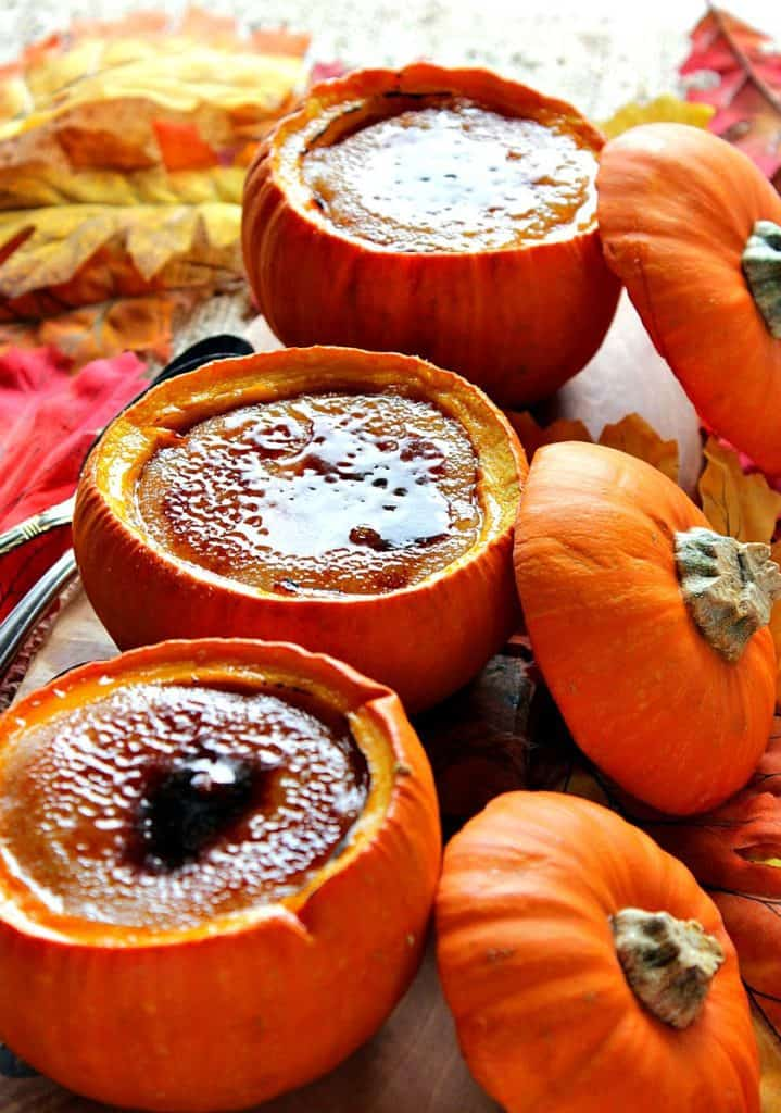 Closeup photo of pumpkin creme brulee baked in real pumpkin shells with autumn leaves and pumpkin tops.
