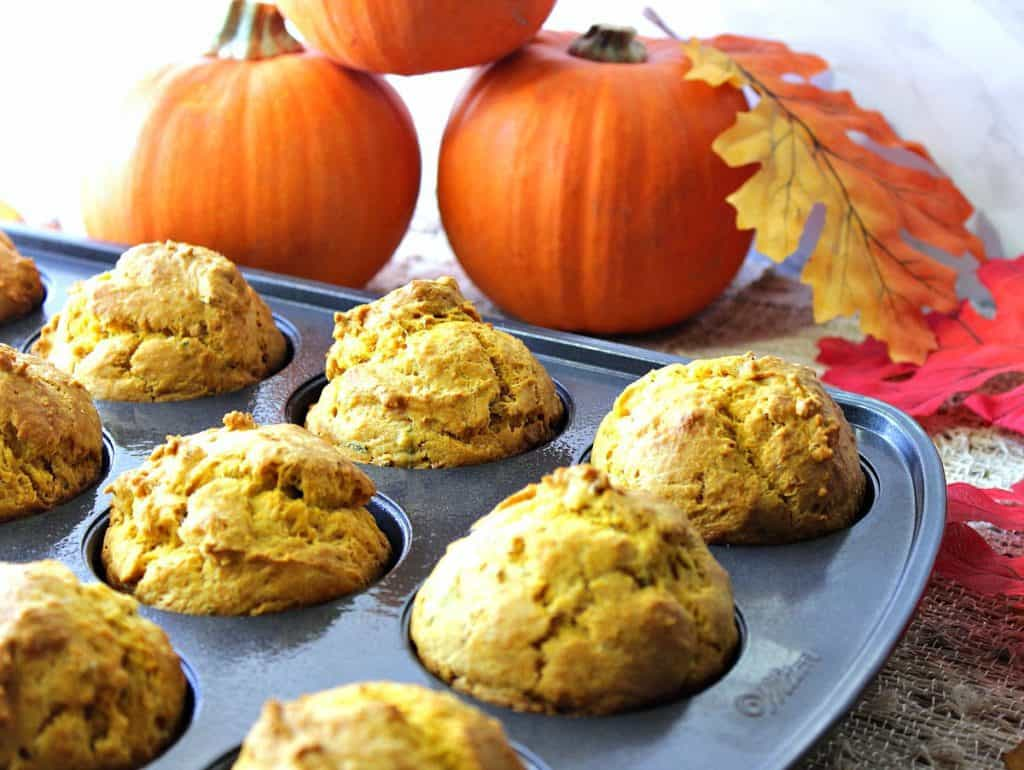 A muffin tin filled with pumpkin sage biscuits with pumpkins and autumn leaves in the background.