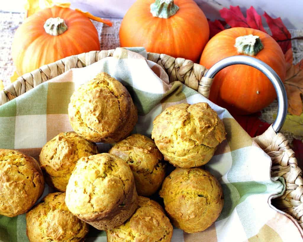 A basket filled with savory pumpkin biscuits with a fall colored checkered napkin.
