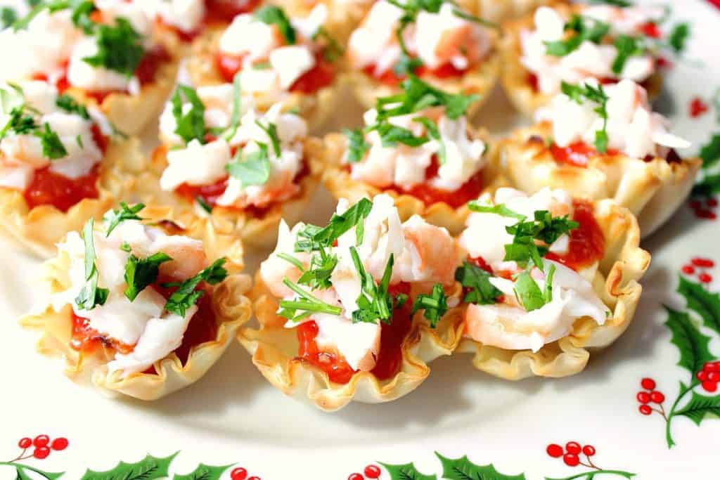 A festive holiday plate with phyllo cups stuffed with shrimp, cream cheese, and cocktail sauce.