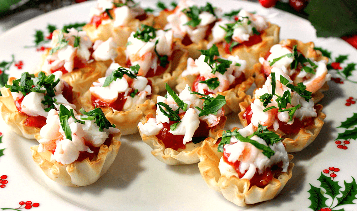 A horizontal photo of a festive plate of shrimp cocktail bites in phyllo cups with cocktail sauce and parsley.