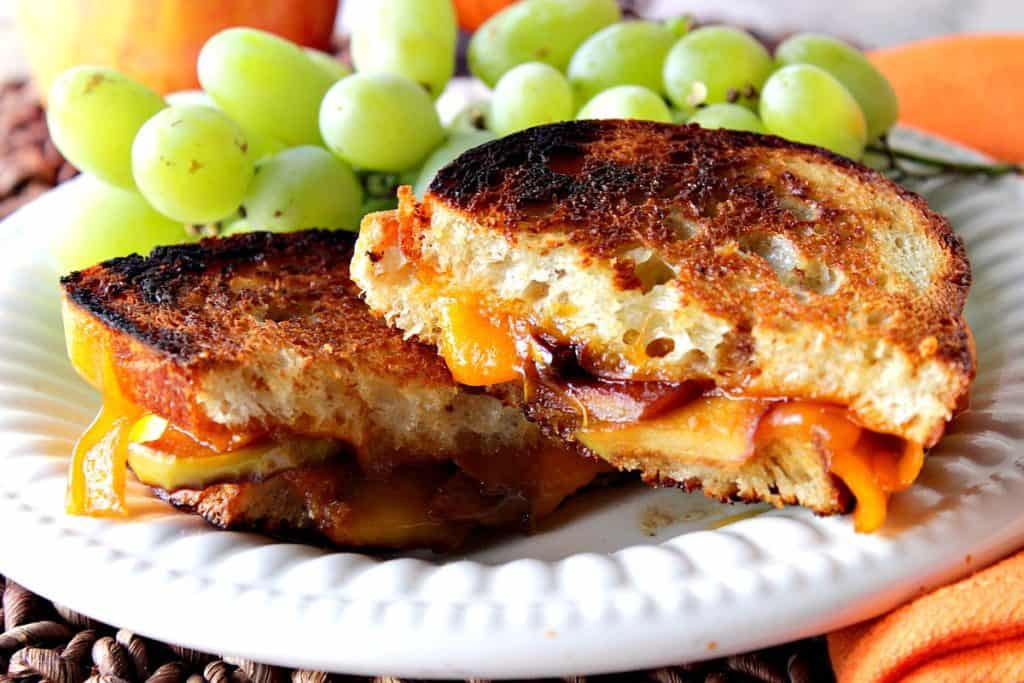A horizontal photo of a grilled cheese sandwich with caramelized apples on a white plate with an orange napkin and green grapes.