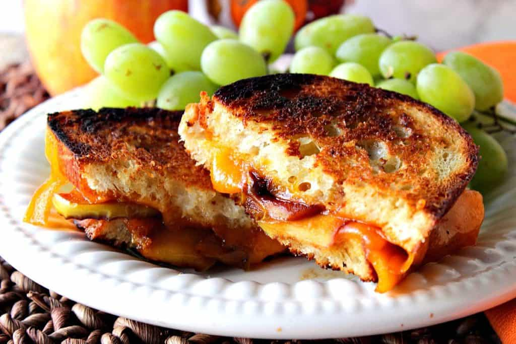 Horizontal photo of a grilled cheese sandwich sliced in half with melted cheddar cheese and caramelized apple slices.