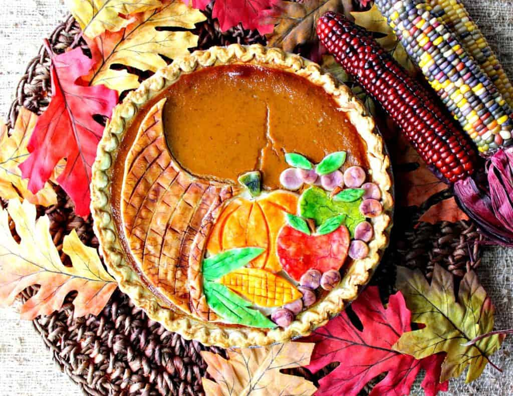 Overhead photo of a colorful cornucopia pie with painted pie crust with autumn leaves and Indian corn.