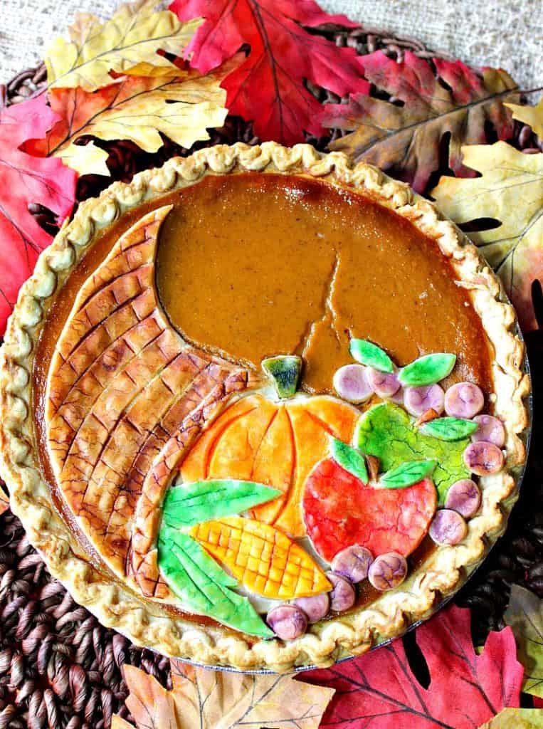 Overhead closeup photo of a colorful painted cornucopia pumpkin pie with corn, apples, grapes, and a pumpkin.
