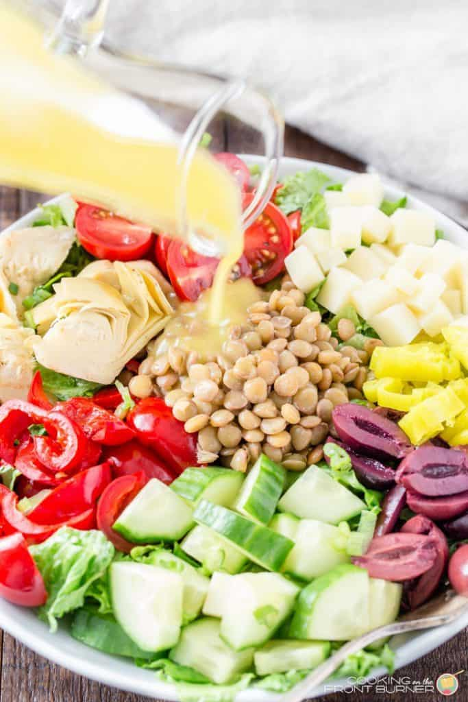 Closeup of dressing being poured over a colorful healthy salad.