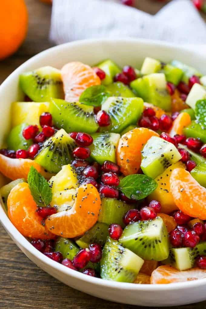 Closeup of colorful fruit salad. Oranges, Kiwi, pomegranate, poppy seeds. Healthy salad recipe roundup.