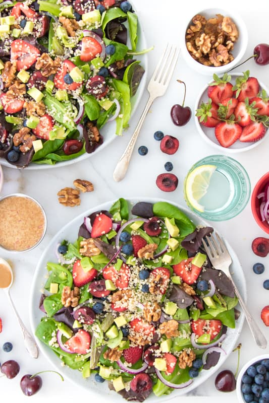 Overhead photo of a lettuce and fruit salad with strawberries and quinoa with nuts and cherries for healthy salad recipe roundup.