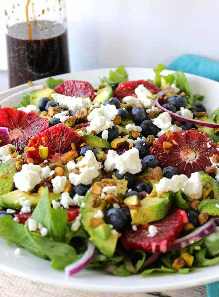 Closeup vertical photo of a blood orange, pistachio, feta, and blueberry salad in a white bowl for healthy salad recipe roundup.
