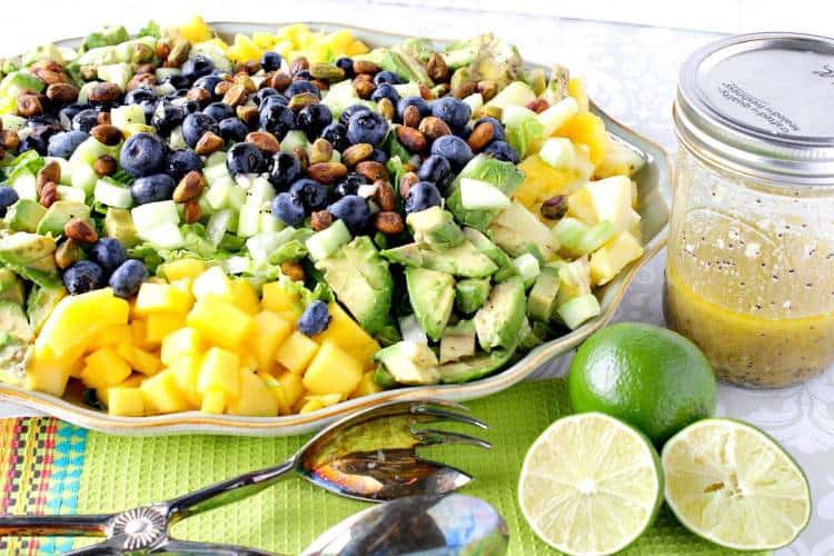 Vertical photo of a heart healthy avocado and mango salad on a platter with lime vinaigrette and blueberries.