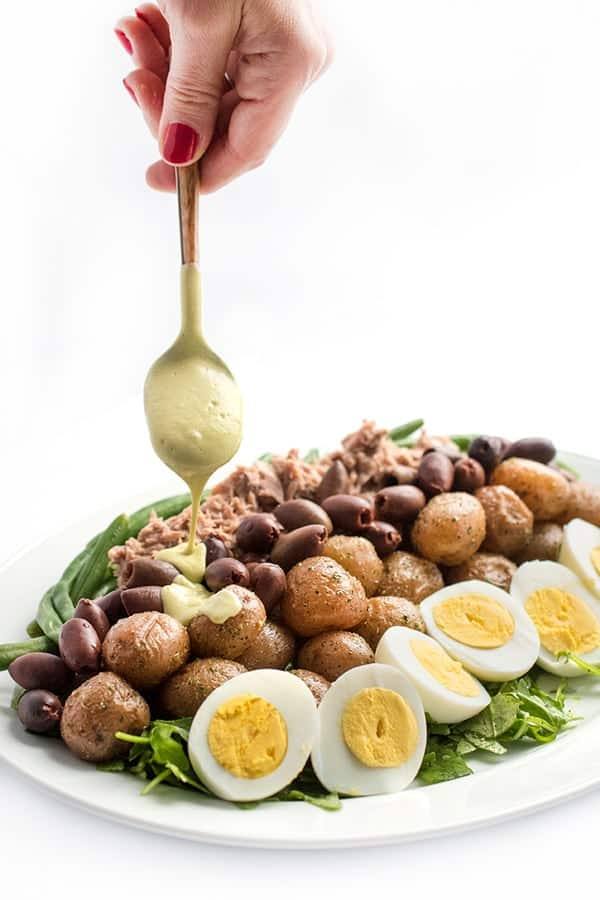 A hand holding a salad dressing spoon drizzling dressing over potato and egg salad with olives for healthy salad recipe roundup.
