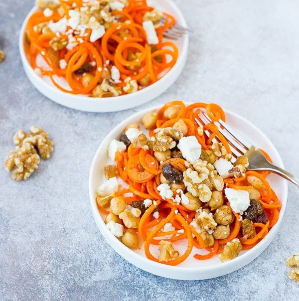 Carrot, walnut, and raisin salad in two white bowls with a fork for healthy salad recipe roundup.