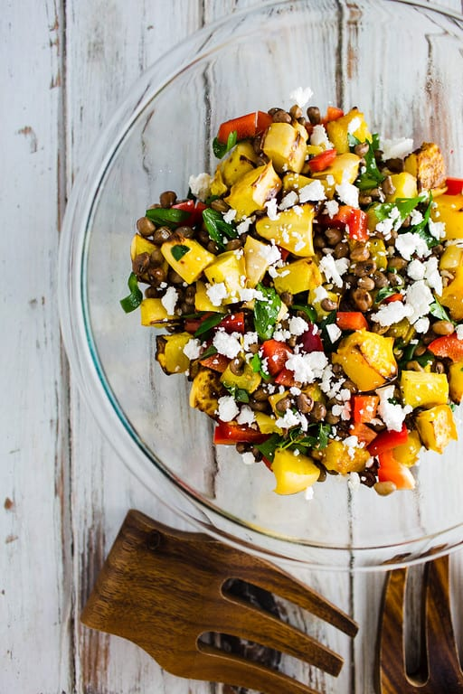 Clear bowl filled with a colorful salad with yellow, green, white and red ingredients. Healthy Salad Recipe Roundup.