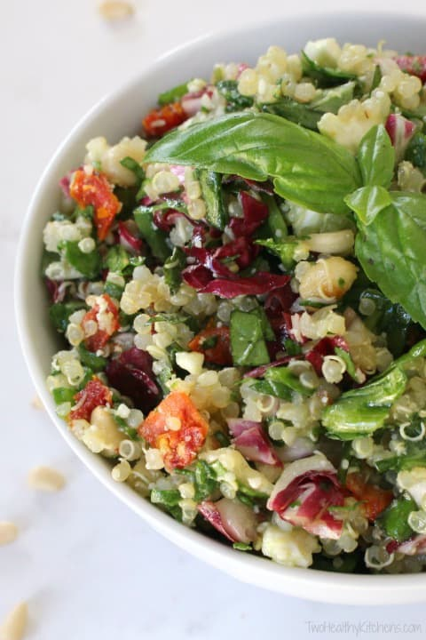 Closeup of quinoa, basil and lettuces in a bowl for healthy salad recipe roundup.