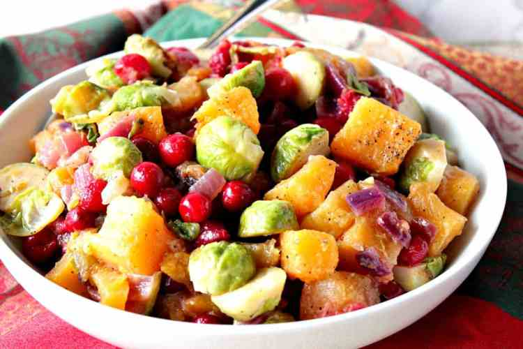Horizontal photo of a colorful bowl of holiday sauteed vegetables with cranberries, Brussels sprouts, and butternut squash. Christmas dinner recipe roundup.