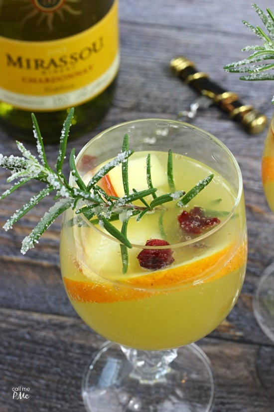 Closeup of a cocktail with fresh fruit and rosemary. New Years eve appetizers and drinks recipe roundup.