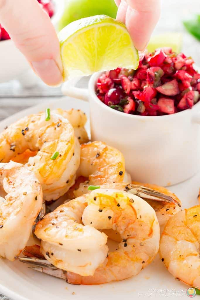 Closeup of cooked shrimp with seasonings on a plate. New Years eve appetizers and drinks recipe roundup.