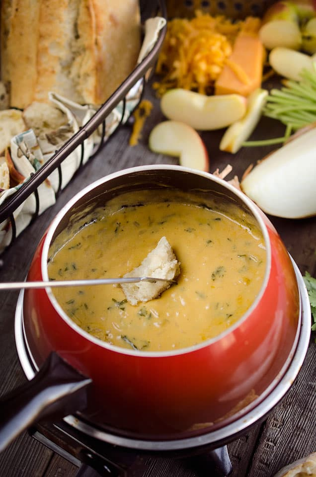 Cheese fondue with a dipper. New Years eve appetizers and drinks recipe roundup.