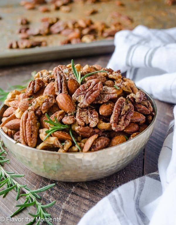 Closeup of nuts in a dish with rosemary. New Years eve appetizers and drinks recipe roundup.