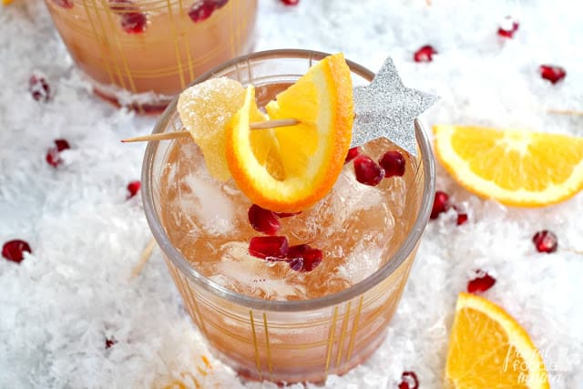 Overhead photo of a cocktail with and orange slice and a star. New Year's eve appetizers and drinks recipe roundup.