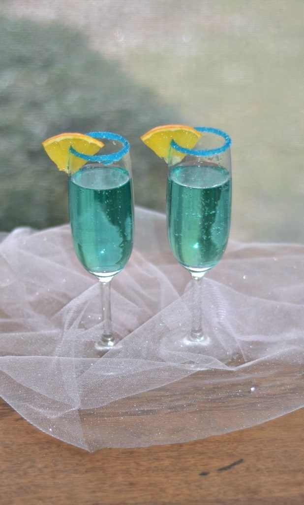 Two blue cocktails with sparkles. New Years eve appetizers and drinks recipe roundup.