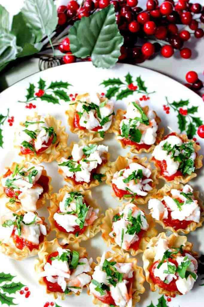 Overhead vertical photo of shrimp cocktail appetizer bites on a festive holiday plate. New Year's eve appetizers and drinks recipe roundup.