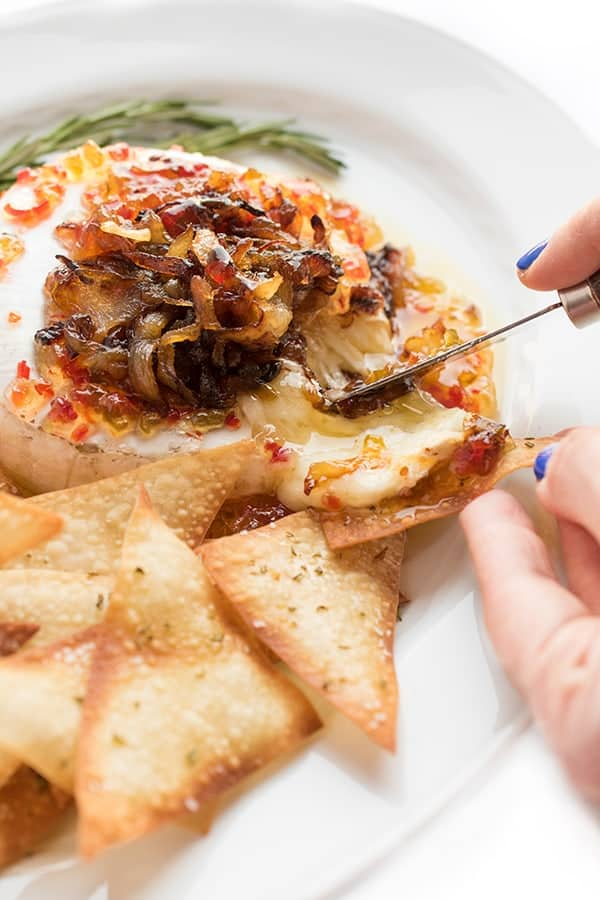 Closeup photo of cheese brie cheese with caramelized onions. New Years eve appetizers and drinks recipe roundup.