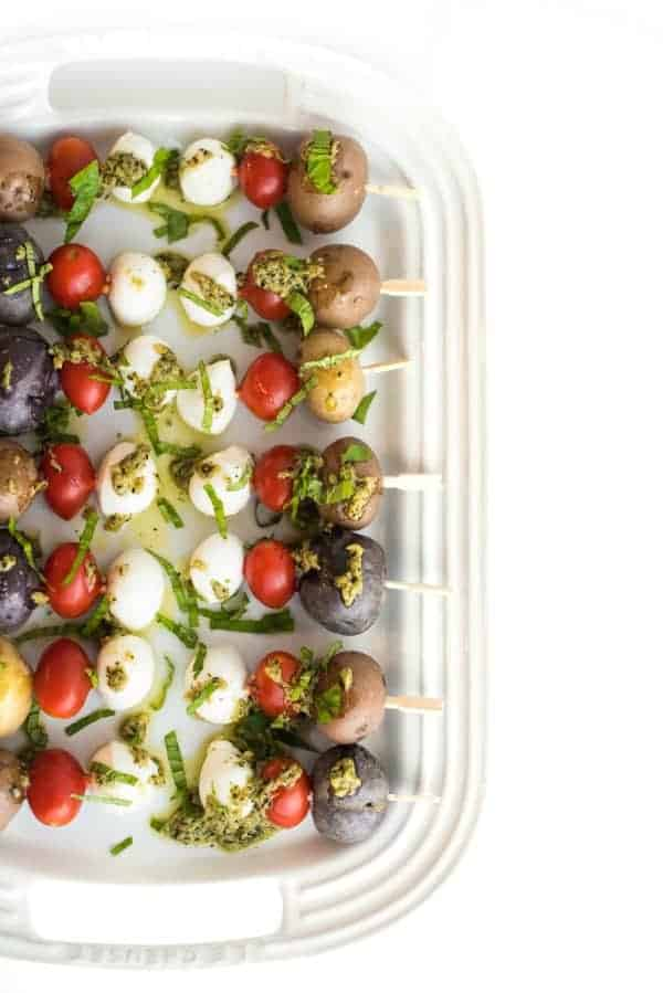 Colorful overhead photo of skewers in a dish. New Years eve appetizers and drinks recipe roundup.