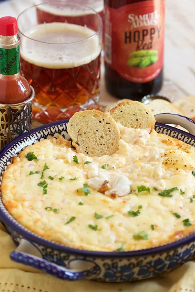 Closeup photo of cheesy dip with crackers. New Year's eve appetizers and drinks recipe roundup.