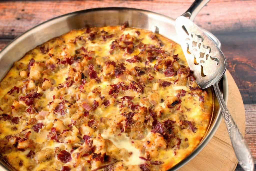 Corned beef hash frittata in a silver skillet with a silver spatula.