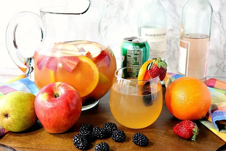 A glass of sangria with blackberries, apples, and oranges with a pitcher in the background along with a few bottles of wine.