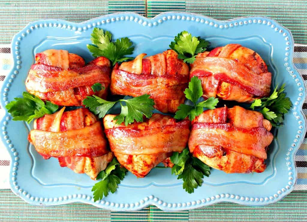 An overhead photo of a blue plate filled with Smoky Sweet Bacon Wrapped Chicken Breast and green parsley