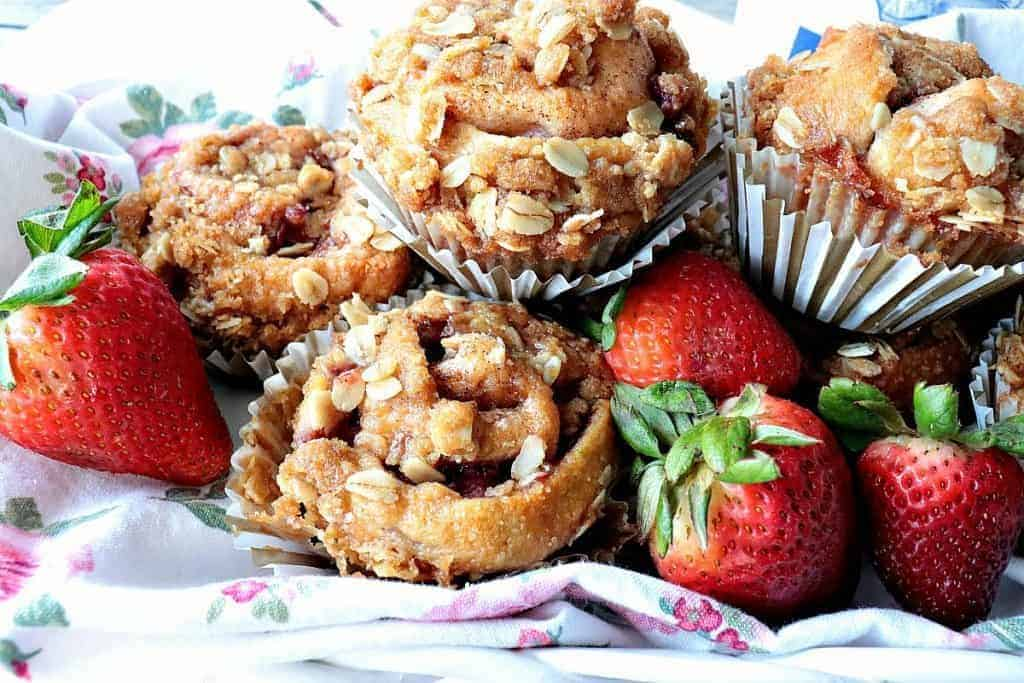 Strawberry muffins piled up on a pretty floral pink napkin with fresh strawberries surrounding the muffins.
