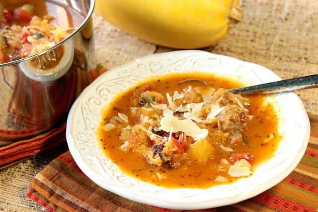 A horizontal photo of a bowl of spaghetti squash soup with Parmesan cheese garnish and a spoon. Soup, Stew & Chowder Recipe Roundup