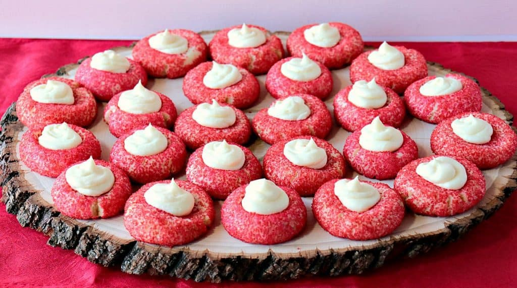 A rustic wooden tray filled with red Cream Cheese Cookies with Creamy Cheesecake topping