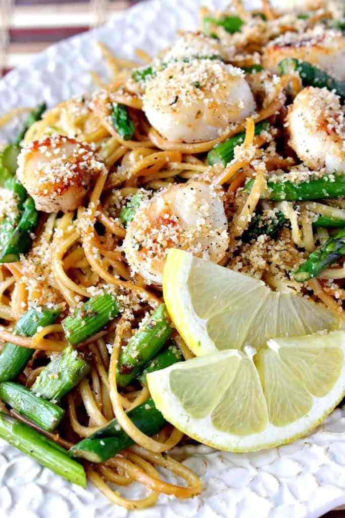 A closeup vertical photo of linguine with scallops, asparagus and buttered breadcrumbs. Valentine's Day dinner recipe roundup.