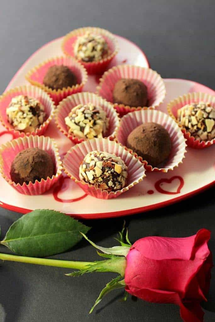 Chocolate avocado truffles on a heart plate for chocolate dessert recipes for valentine's day roundup.