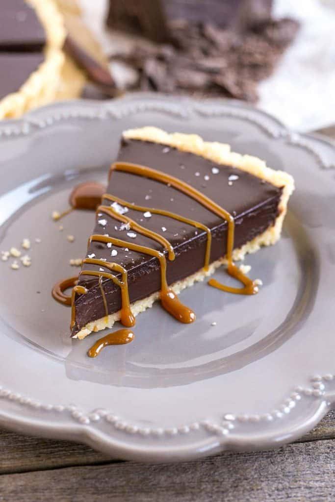 A slice of a chocolate tart on a plate for Valentine's Day chocolate dessert recipes collection