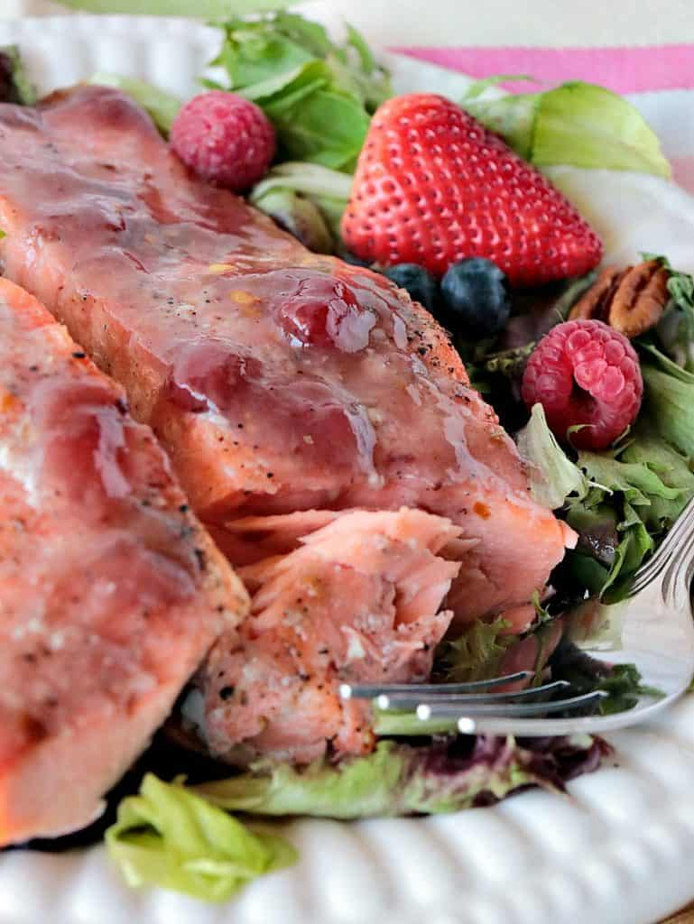 Closeup photo of flaked salmon on a white plate with a strawberry glaze.