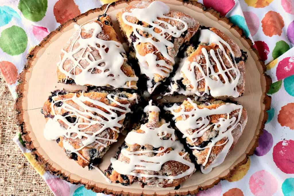 An overhead photo of a wood plate filled with Blueberry Lemon Scones drizzled with icing.