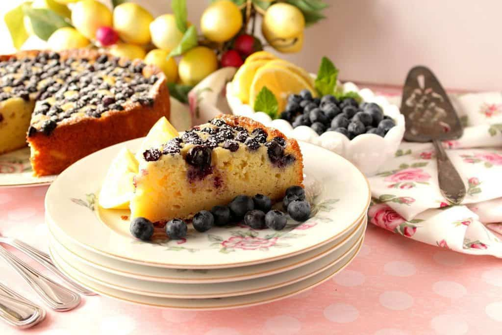 Slice of lemon ricotta cake on a stack of china plates on a pink tablecloth.