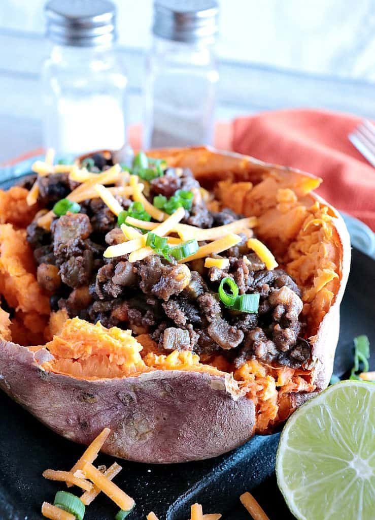Closeup Tex-Mex Stuffed Sweet Potatoes with Ground Beef, Beans, cheese and green onions.
