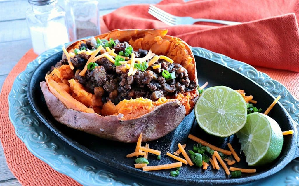 Spicy Tex-Mex Stuffed Sweet Potatoes on a blue platter with lime slices and cheddar cheese.
